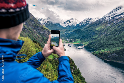 Papel de parede tourist takes photo of Geiranger fjord on smartphone