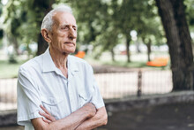 Close Up Portrait Of Senior Adult Man With Gray Hair Outdoors In The City Park.