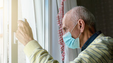 Aged Man In Blue Mask Glances Relatives Standing By Window