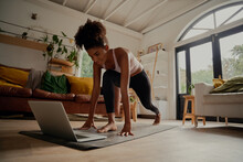 Happy Woman Watching Video On Laptop While Exercising On Yoga Mat At Home - Lock Down Workout