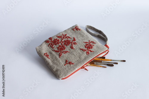 Makeup bag made from linen cloth and embroidered with red threads Fototapeta