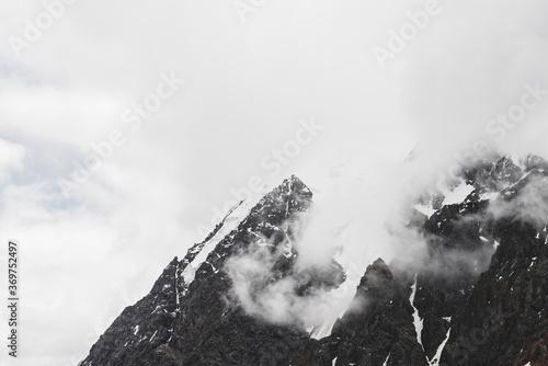 Obraz na plátně Atmospheric minimalist alpine landscape with hanging glacier on snowy rocky mountain peak