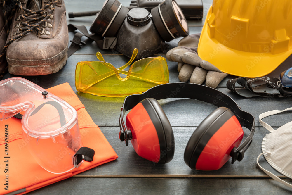 Fototapeta Work safety protection equipment background. Industrial protective gear on wooden table