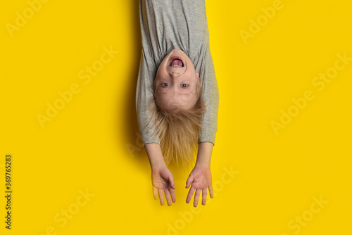 Fototapety, obrazy: Surprised fair-haired boy hanging upside down with arms outstretched. Portrait of child on bright yellow background