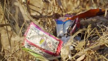 Pile Of Empty Food Packs On The Ground With Surrounding Dried Leaves