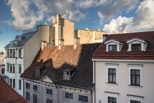 Early Morning View Of Old Houses Roofs, Windows, Dormers, Cornices, Chimneys, Chimney Stacks Chimney Pots, Towers, Antennas In Old Town  Of Riga, Latvia.