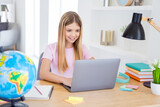 Photo of positive kid girl sit table desk study remote use smartphone have online communication lesson with tutor in house indoors