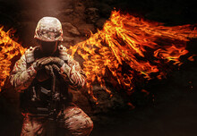 Soldier In Uniform Kneeling With Fire Wings On His Back.