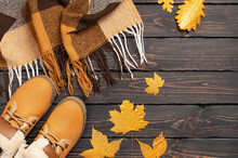 Autumn Fashion Concept. Brown Orange Leather Women Boots With Fur, Checkered Warm Plaid, Golden Autumn Leaf On Brown Wooden Background Top View. Fashionable Women's Footwear. Cozy Fall Composition