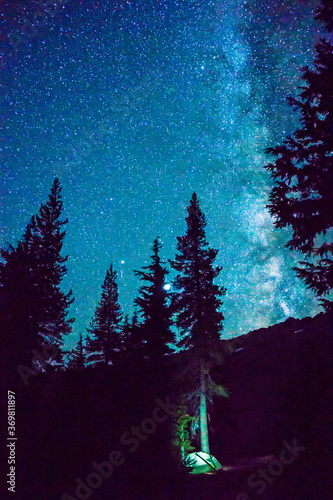 Papel de parede The Milky Way galaxy shines in the night sky over a small illuminated camping tent nestled among the trees