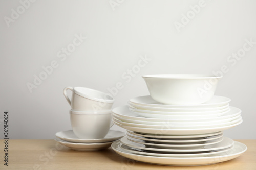 Obraz Clean plates, bowl and cups on wooden table against white background. Space for text - fototapety do salonu
