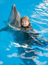 The Small Girl Hugs A Dolphin At Dolphin Therapy Session