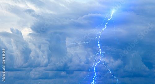 Fotografia Lightning strikes between blue stormy clouds.
