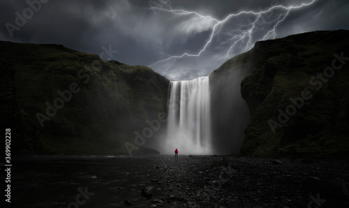 Fotografie, Obraz Man in front of huge waterfall with storm rays