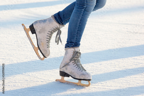 Photo legs of a girl in blue jeans and white skates on an ice rink