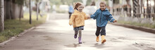 Children Brother And Sister Play Autumn Rain / October Weather Little Children Walk In The City