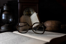 Old Worn Glasses Resting On An...