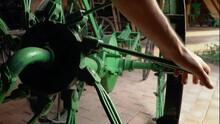 Male Hand Rotating Piece Of Green Coloured Vintage Agricultural Equipment.