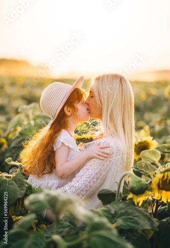 Obraz Happy mother kisses her little red-heired daughter in a field with yellow sunflowers on sunset. - fototapety do salonu