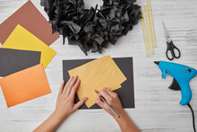 Female Hands Draw A Pumpkin On A Yellow Paper To Decorate A Greeting Card For Helloween Party On A Gray Wooden Table. Flat Lay