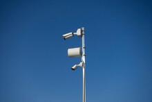 White Surveillance Cameras On White Sky