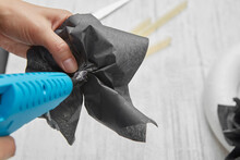 Female Hands Make A Black Flower From Paper With An Electric Glue Gun Over A Gray Wooden Table.