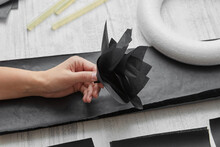 Female Hand Hold A Black Paper Flower Above Gray Wooden Background With Materials For Handcraft Creativity. Flat Lay
