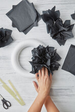 Cut Into Square Pieces Of Black Paper Tyshyu And Handmade Black Flowers On A Round Frame That Attach Female Hands To It On A Gray Background. Flat Lay.