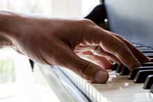 A Male Hand Resting On A Piano...