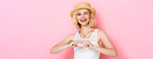 Panoramic Shot Of Woman In Straw Hat Winking Eye And Showing Heart Sign With Hands On Pink