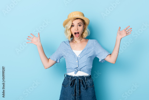shocked young woman in straw hat gesturing on blue Canvas-taulu