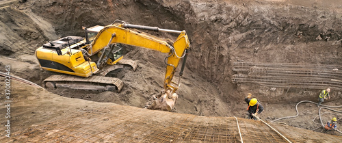 Photo Panoramic view of an excavator vehicle in construction site among an abseil worker
