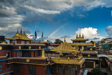 Bright Rainbow Arc Over A Buddhist Monastery With Gilded Roofs Against The Blue Sky, Dramatic Gray Clouds And Mountains In The Background.