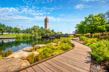Summer Day Along The Spokane River In Riverfront Park With The Clock Tower, Pavilion And Walking Path In View.