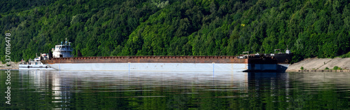 Photo barge goes on the water against a backdrop of green trees