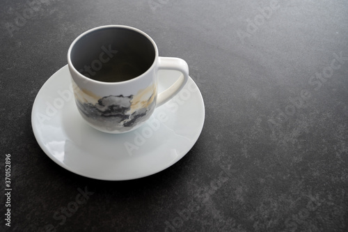 Obraz na plátně A coffee cup placed on a white saucer placed on a dark stone table with copy spa