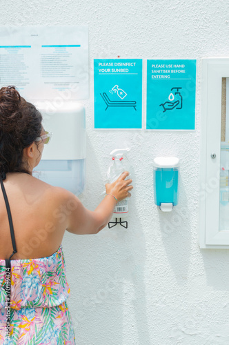 Fotografia Coronavirus safety measures in the pool: woman using a bottle of hand sanitizer to clean sunbed and hands