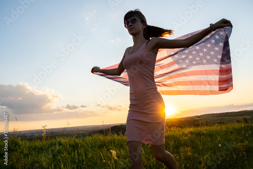 Photo Happy young woman posing with USA national flag standing outdoors at sunset