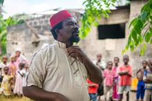 An African Older Man, The Mayor Of His Village In Red Muslim Taqiyyah Hat And White Dress. Small Remote Village In Tanzania, Pemba Island, Zanzibar Archipelago