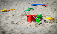 Colourful Buckets And Spades Left Laying On A Sandy Beach.