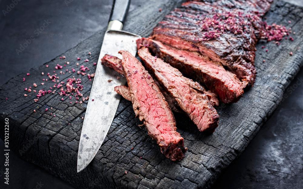 Gegrilltes Wagyu Bavette Steak vom Rind mit Rotwein Salz angeboten als close-up auf einem verkohlten Holz Board