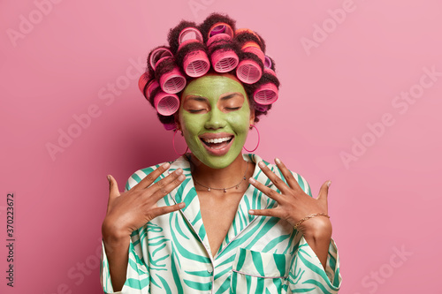 Portrait of cheerful lady with green beauty mask for healthy skin, keeps eyes cl Wallpaper Mural