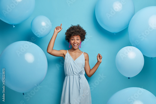 Billede på lærred Upbeat cheerful festive woman with hollywood smile, laughs out of joy, moves carefree and dances to music, has fun, makes happy holiday photo, celebrates anniversary, surrounded by balloons