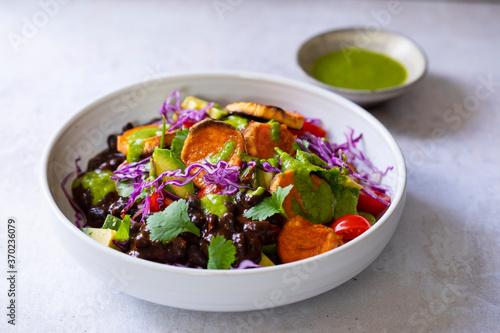 Fototapeta Vegan bowl with black beans, roast sweet potatoes, red cabbage and avocado obraz