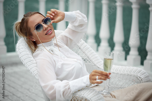 Papel de parede A beautiful glamorous lady in sunglasses in a luxurious white blouse and trousers poses sitting with a glass in her hand against the balusters of the railing of her Palace
