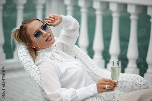 Tela A beautiful glamorous lady in sunglasses in a luxurious white blouse and trousers poses sitting with a glass in her hand against the balusters of the railing of her Palace