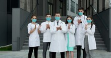 Medical Staff From The Hospital Who Are Fighting Coronavirus Applaud Back The People And Police Officers For Their Support. Corona Virus And Healthcare Concept. Doctors With Face Masks