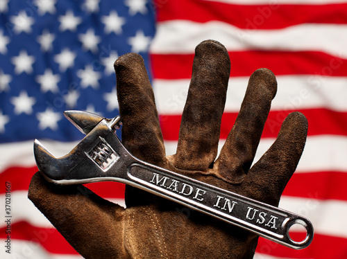 Fototapeta Old worn work glove holding adjustable wrench with Made in USA text