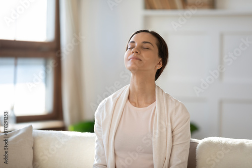 Obraz Mindful young woman breathing fresh air with closed eyes, sitting on sofa alone indoors. Peaceful happy millennial girl meditating in living room, enjoying affirmations or lazy free weekend time. - fototapety do salonu