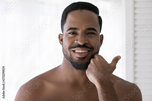 Head shot portrait smiling satisfied African American young man touching beard after shaving, applying aftershave lotion or cream, enjoying skincare procedure, standing in bathroom after shower
